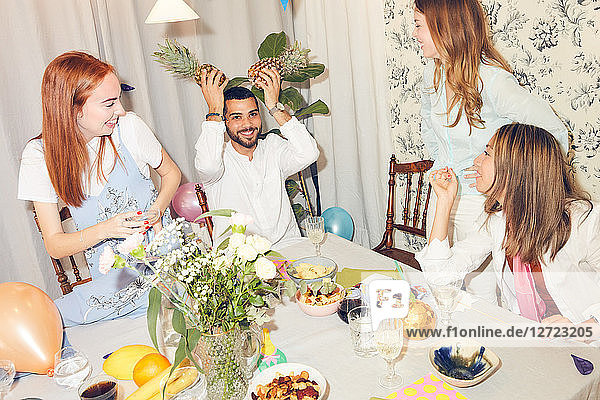 Playful man holding pineapples while sitting amidst female friends at home during dinner party