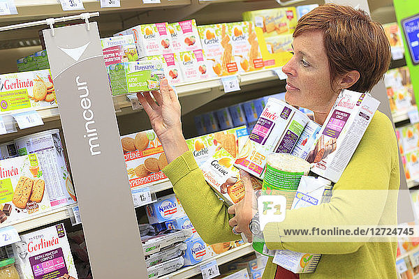 France  woman in a supermarket. Diet items.