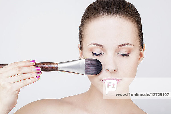 Portrait of a young woman applying a make-up brush on face  eyes closed