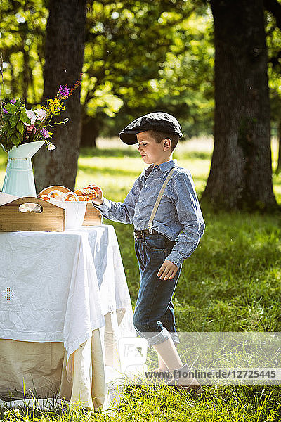 Young boy holding a chocolate croissant in his hand during a brunch in the country. Mandatory credit: Design culinaire : food-design-studio.fr