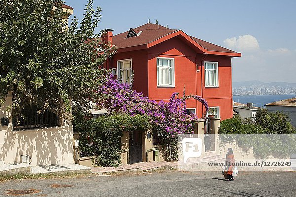 Woman in front of the traditional wooden house covered with flowers in Heybeliada-Halki  Prince Islands  Marmara Sea  Istanbul  Turkey  Europe