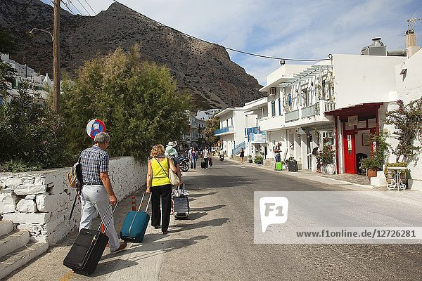 Tourists with bags walking to the port in Kamares village  Sifnos Island  Cyclades Islands  Greek Islands  Greece  Europe