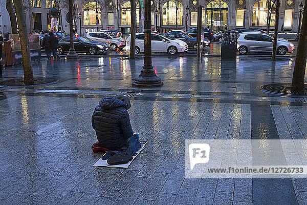 France  Paris  Avenue des Champs-Elysees  a beggar in the rain.