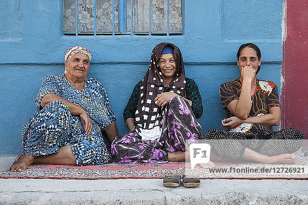 Three aged woman sitting on a carpet in the main street of Gypsy district of Canakkale  Turkey