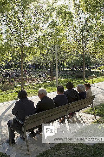 France  Paris  Parc Clichy-Batignolles-Martin Luther King  seniors sitting on a bank  back view