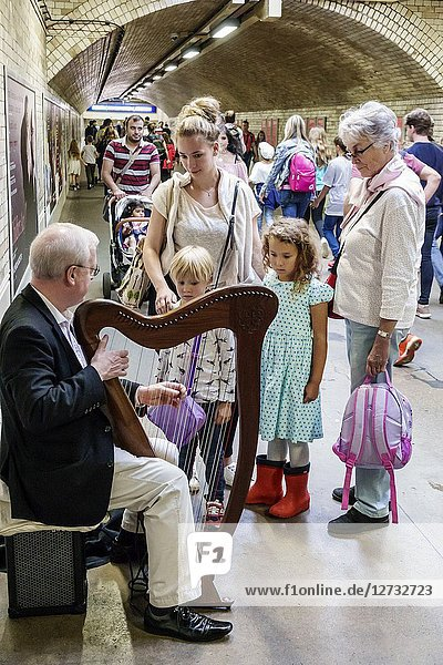 United Kingdom Great Britain England  London  Kensington  South Kensington Underground Station subway tube  public transportation  inside  musician  playing tips  busker  man  senior  harp  woman  girl  boy  child  family  watching