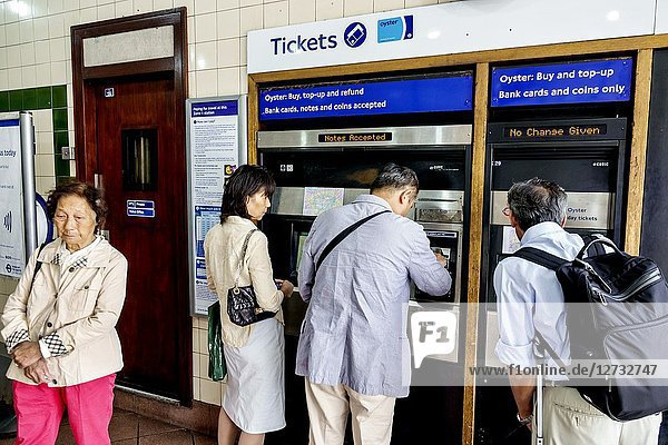 United Kingdom Great Britain England  London  South Bank  Lamberth North Underground Station subway tube  mass transit  public transportation  inside  self-service ticket vending machines  oyster card sales  Asian  man  woman  paying