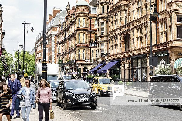 United Kingdom Great Britain England  London  West End City Westminster Mayfair  South Audley Street  historic buildings  flats  shops  pedestrians  woman  taxi