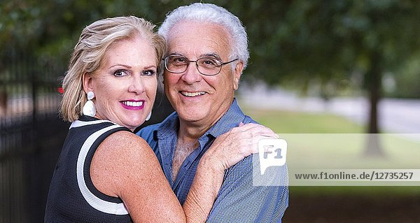 A happy mature adult couple hugging and looking at at the camera.