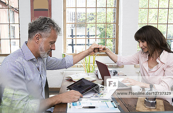 Mature couple high fiving in home office  using laptop and digital tablet
