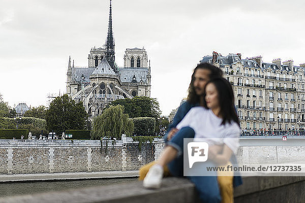 France  Paris  couple sitting on wall at river Seine in front of Notre Dame