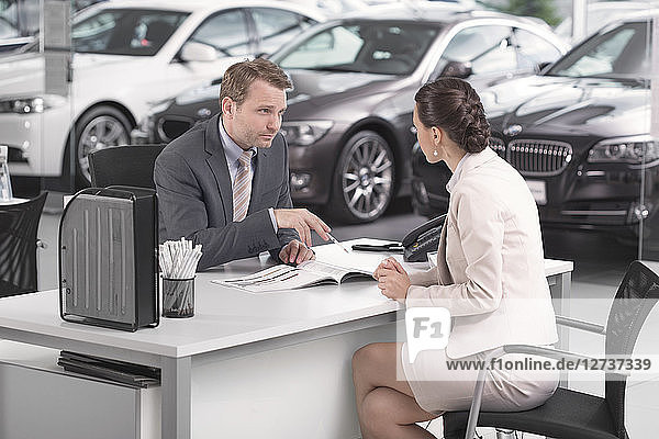 At the car dealer  Salesman talking to client