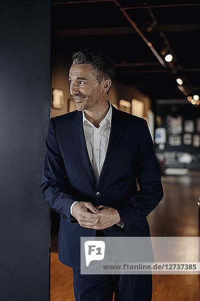 Smiling businessman in office looking sideways