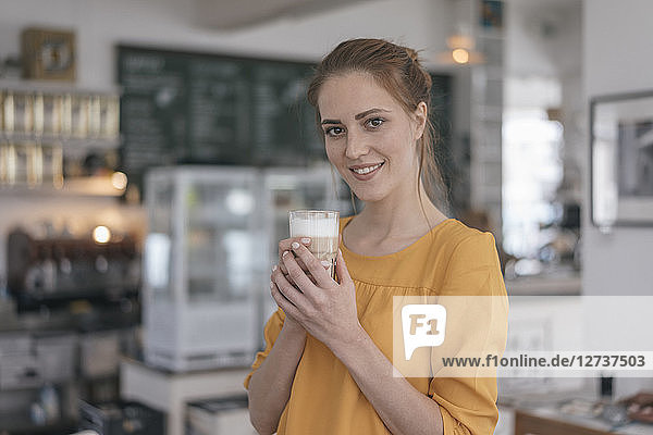 Young business owner standing in her coffee shop  drinking coffee