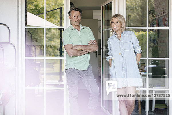 Portrait of smiling mature couple standing at French window