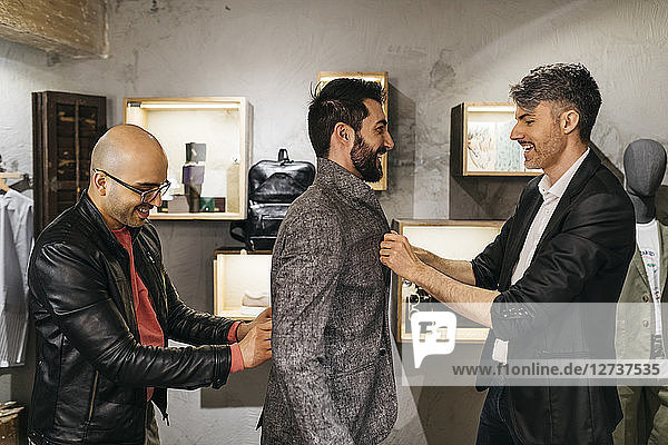 Two men working on new stylish look for handsome man in showroom