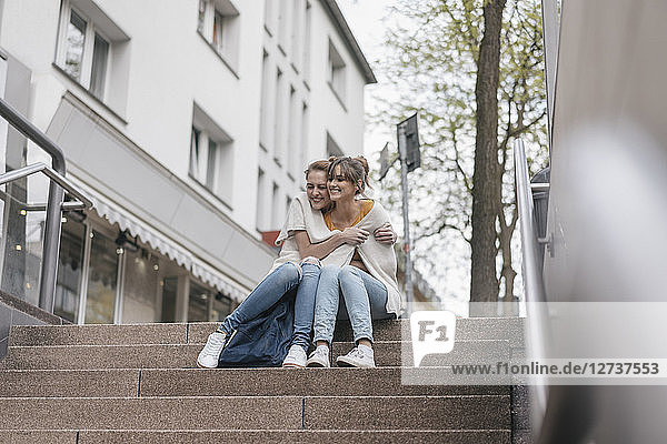 Friends sitting on stairs in the city  sharing cardigan