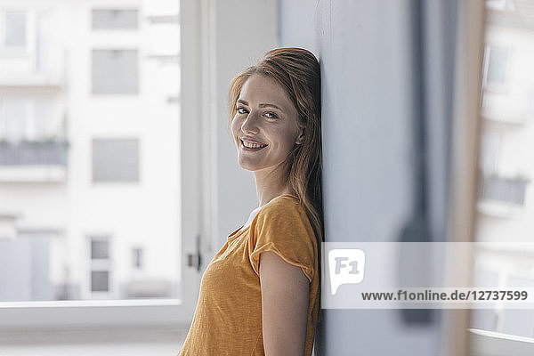 Happy woman leaning on wall