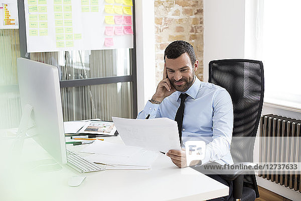 Businessman in office looking at documents at desk