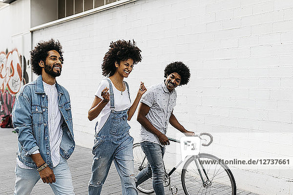 Three friends with racing cycle walking on the street