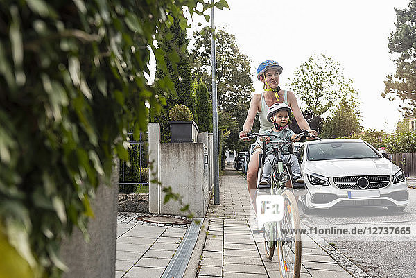 Mother and daughter riding bicycle  daughter wearing helmet sitting in children's seat