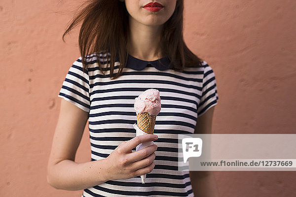 Young woman holding ice cream cone with one scoop  partial view
