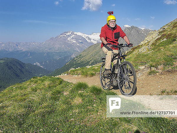 Italy Lombardy  Passo di Val Viola  Man riding e-bike in the mountains with action cam on his helmet