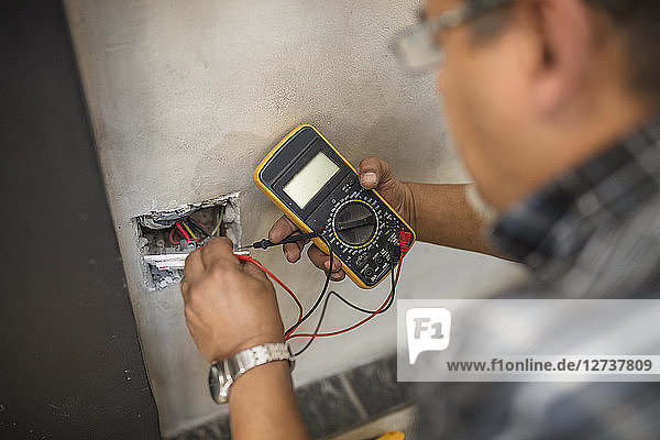 Man checking wall socket with electric current
