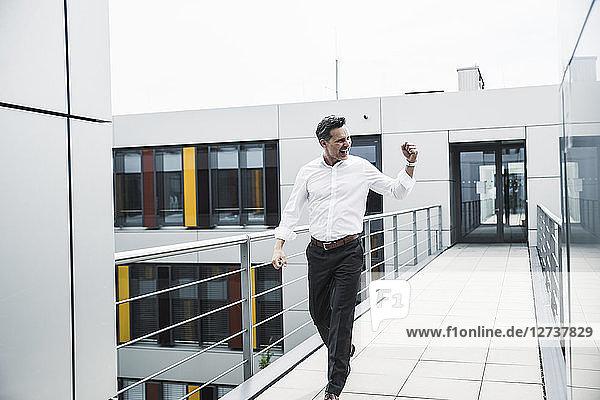 Cheering businessman walking on skywalk at office building