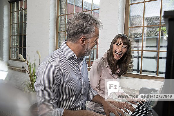 Mature couple having fun at home  playing the piano