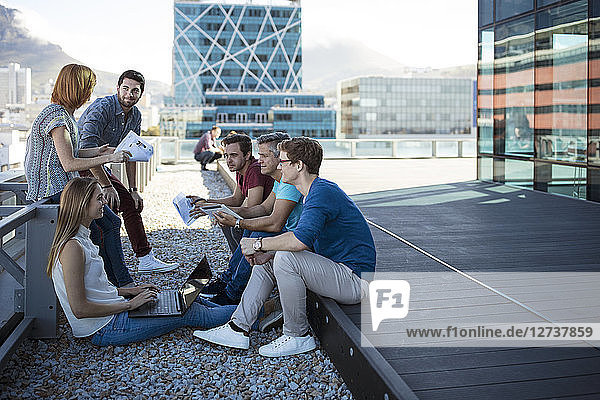Business people having a casual meeting on a rooftop terrace
