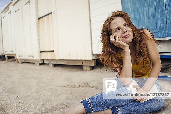 Redheaded woman sitting in front of beach cabin  reading a book