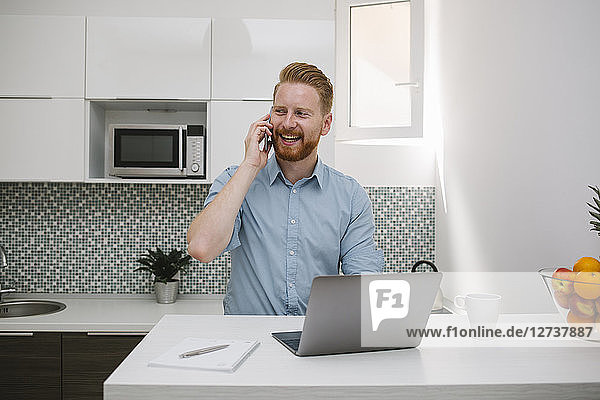 Businessman with laptop talking on the phone in his kitchen