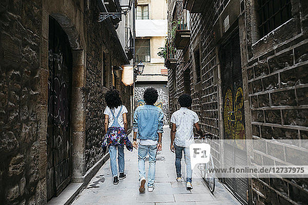 Spain  Barcelona  back view of three friends walking down an alley