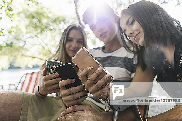 Three friends looking at cell phones outdoors