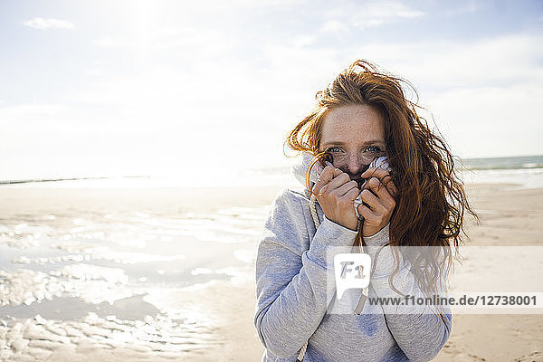 Redheaded woman enjoying fresh air at the beach