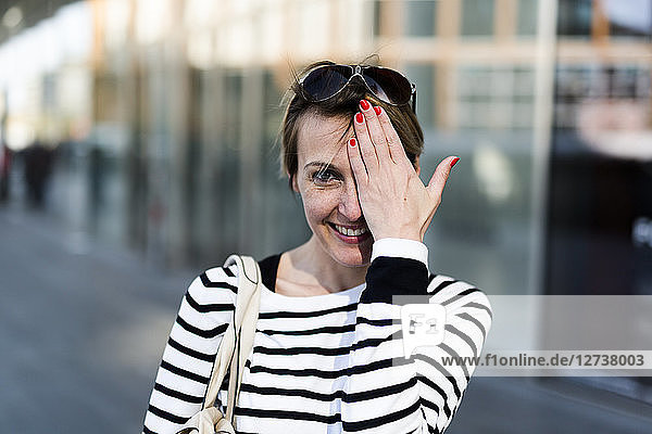 Portrait of smiling woman covering eye with her hand