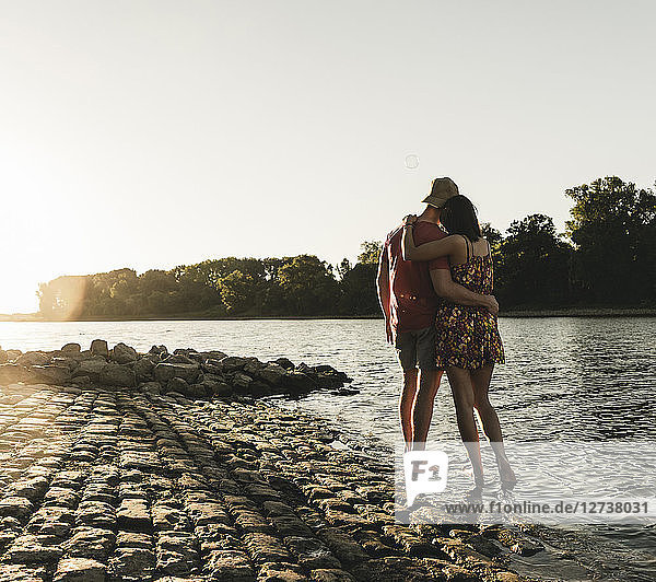 Rear view of young couple embracing at a river at sunset