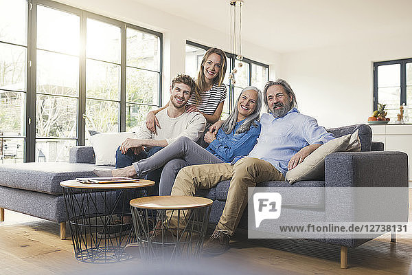Senior couple with family sitting on couch
