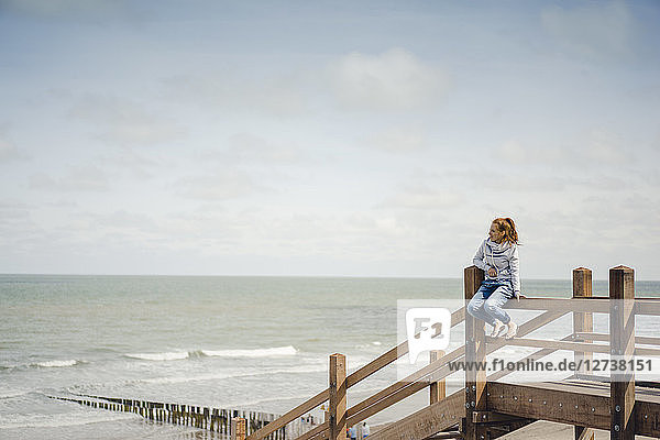 Woman sitting on fence at the beach  relaxing at the sea