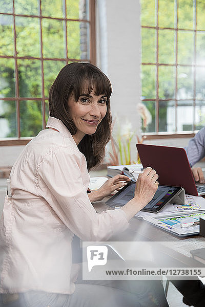 Mature woman sitting in home office  using digital tablet