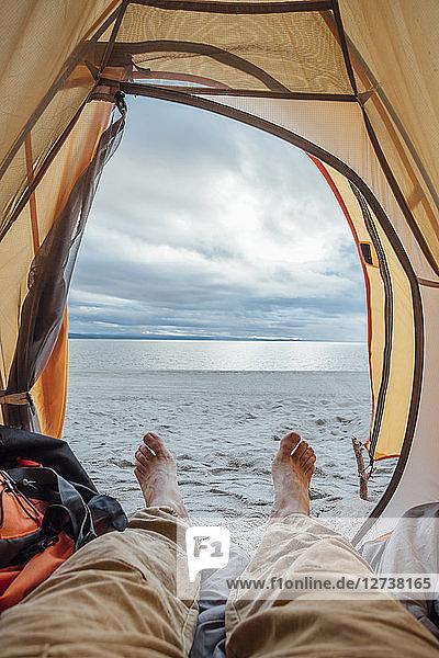 Feet of man,  lying in tent on beach