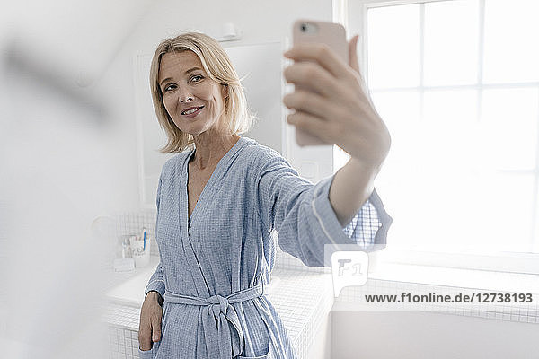 Smiling mature woman taking a selfie in bathroom