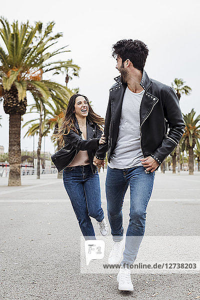 Spain  Barcelona  happy young couple running on promenade with palms