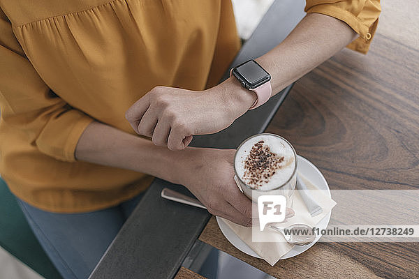 Woman wearing smartwatch  sitting in cafe  drinking coffee