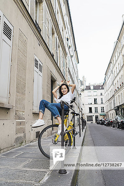 Playful young woman on bicycle at the roadside