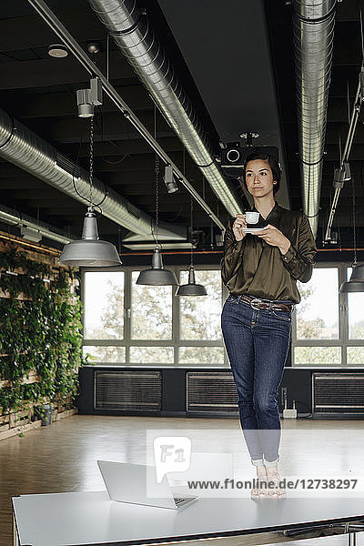 Young woman in office standing on table with cup of coffee