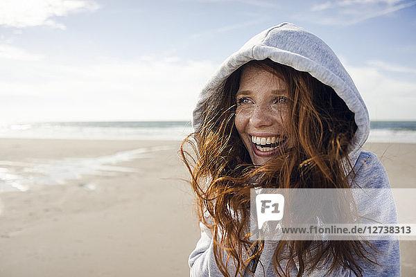 Woman having fun on a windy beach  wearing hood