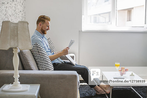 Laughing businessman reading newspaper in his living room