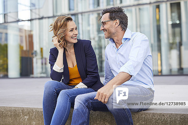 Two business people sitting outdoors talking